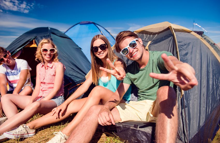 Group of teenage boys and girls at summer music festival, sitting on the ground in front of tents